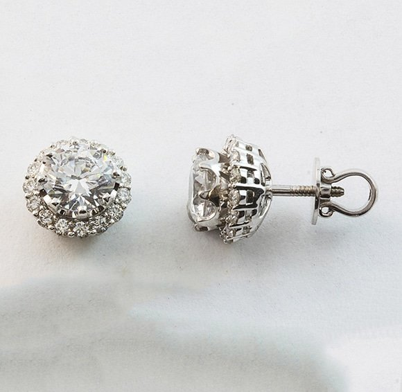 Diamond solitaire studs with removable halo surrounds in 18 carat white gold.