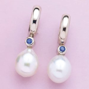 Pearl and sapphire drops suspended from hinged 'Huggie' style earrings.