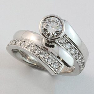 Diamond set band with a rubbed-in brilliant cut diamond termination. An interlocking wedding band completes the picture.